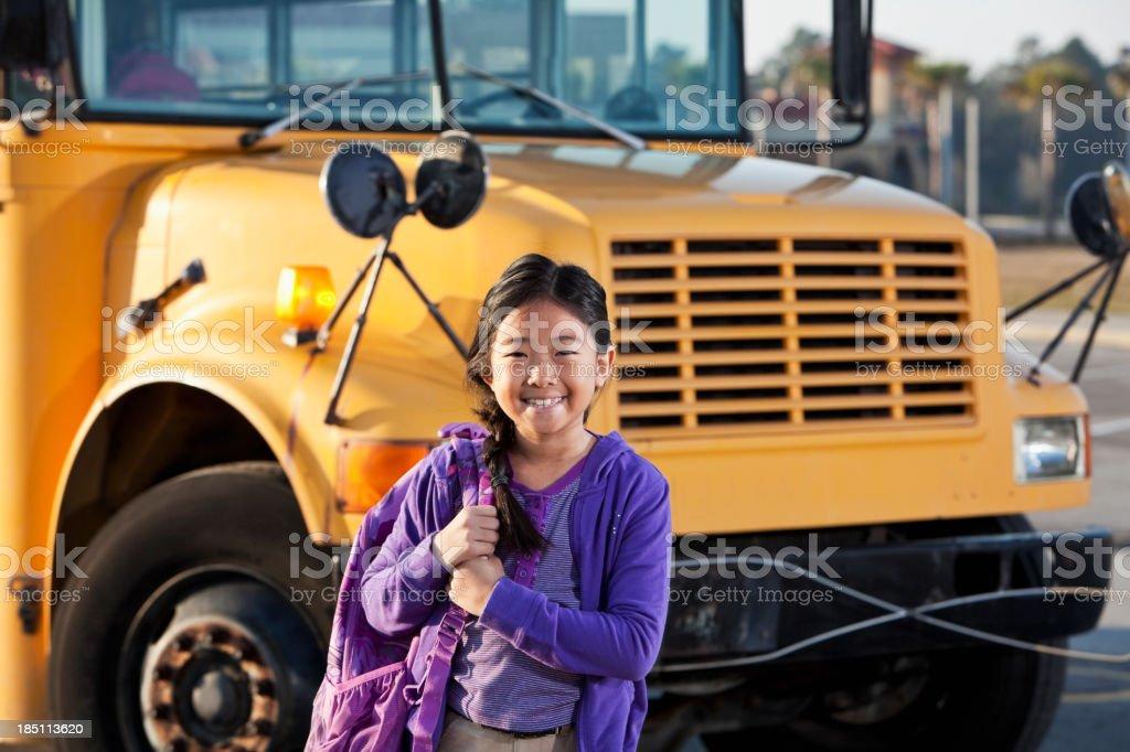 Girl in front of school bus stock photo