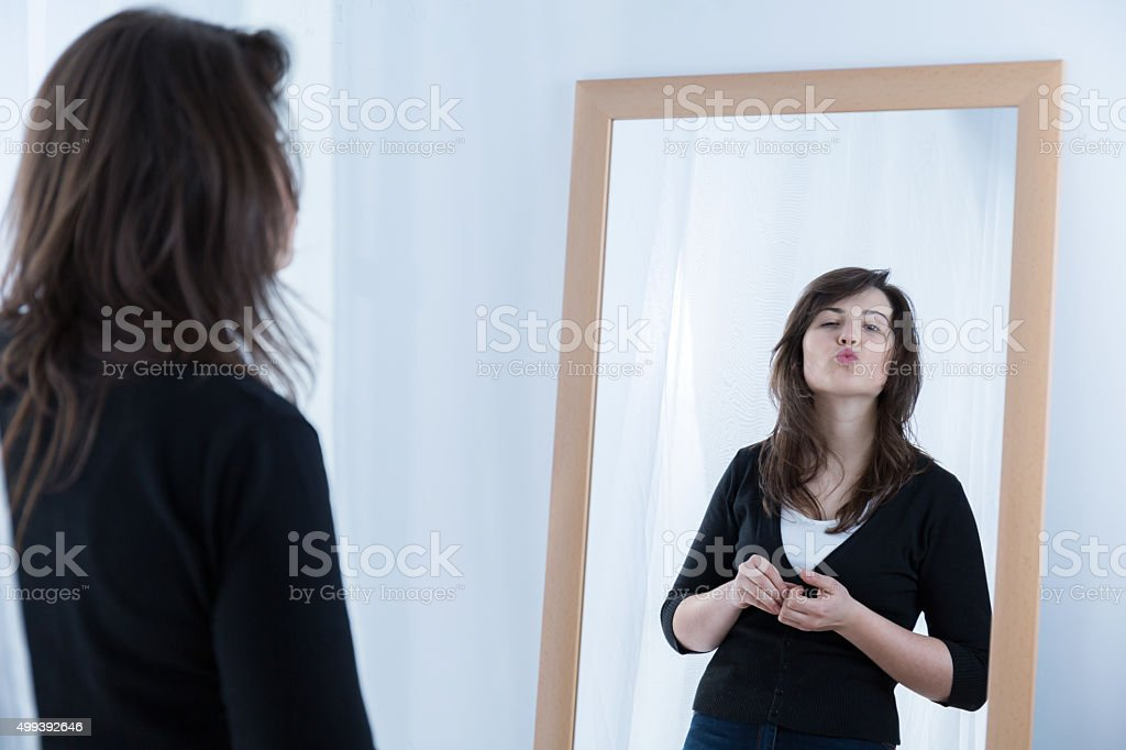 Girl in front of the mirror stock photo