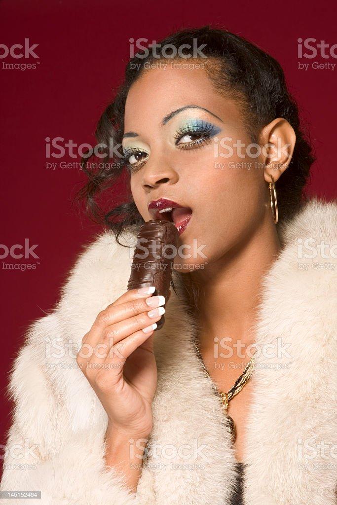 Girl in fur coat eat chocolate royalty-free stock photo