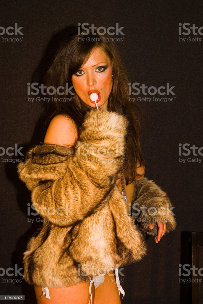 girl in fur with lollipop stock photo