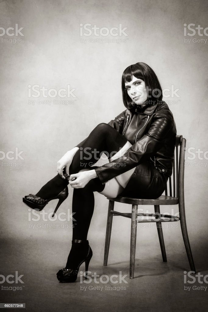 Girl in gaiters and mini skirt sitting on a chair, fastened shoes stock photo