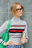 Girl in glasses with backpack at gray wall