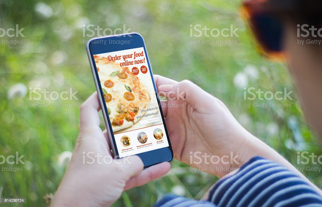 girl in grass holding her smartphone  ordering fast food stock photo
