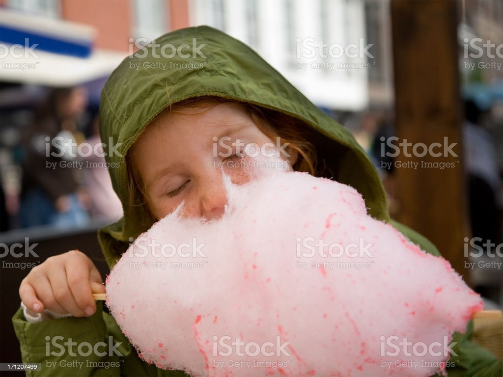 girl in green, eating cotton candy royalty-free stock photo