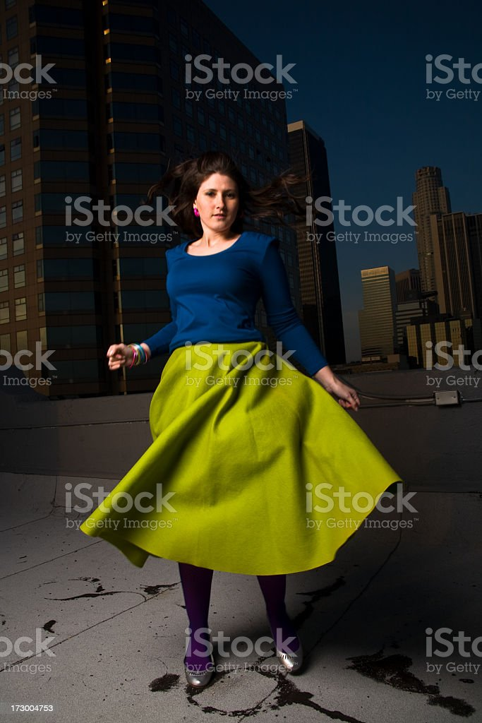 Girl in Green Skirt Spinning on Rooftop stock photo