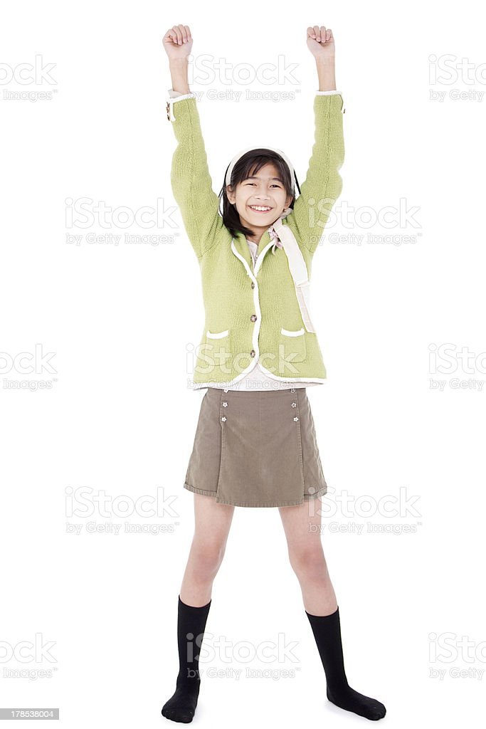 Girl in green sweater and skort standing, arms raised royalty-free stock photo