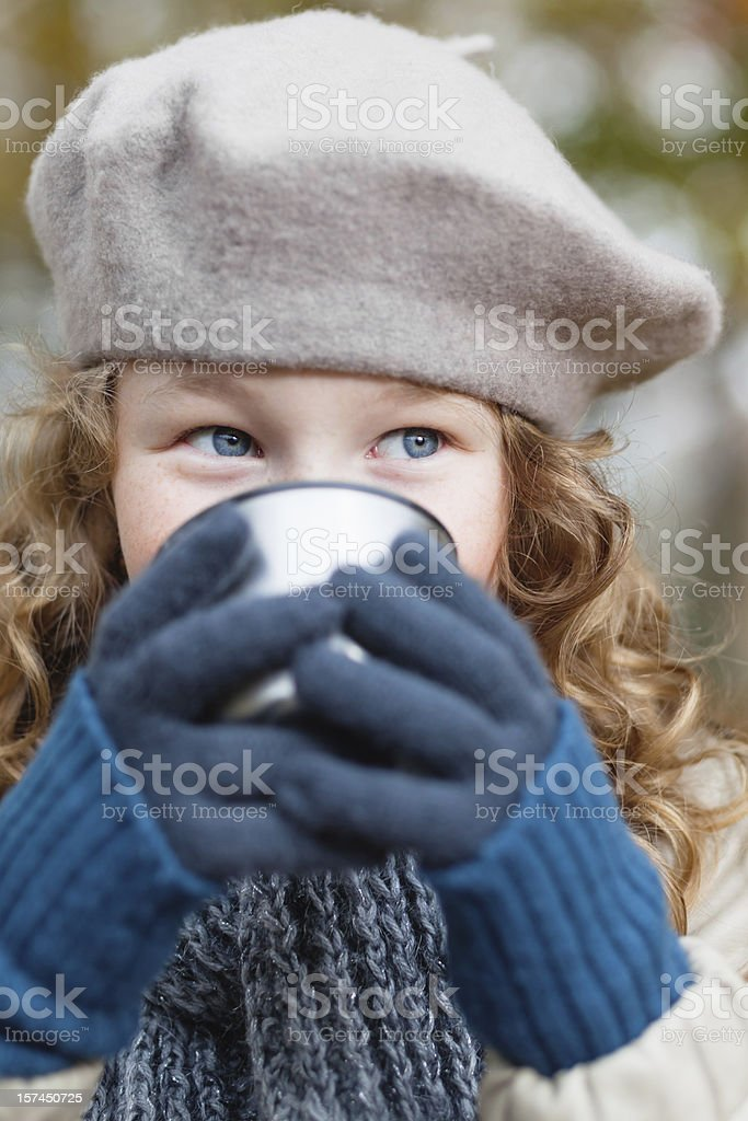 Girl in grey beret drinking from flask cup royalty-free stock photo
