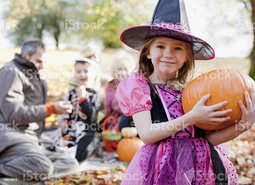 Girl in Halloween costumes holding pumpkin stock photo