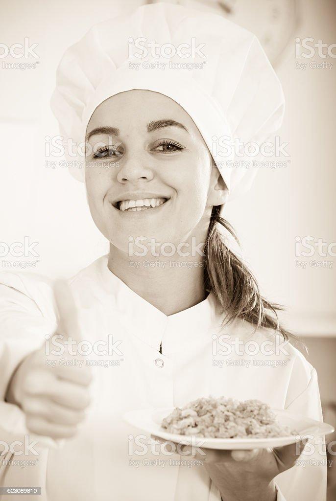 girl in hat and white coat showing porridge stock photo
