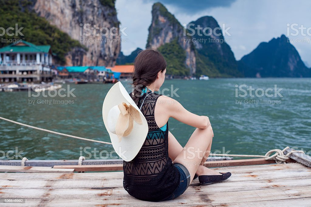 Girl in hat sitting on pier and enjoy view. Young stock photo