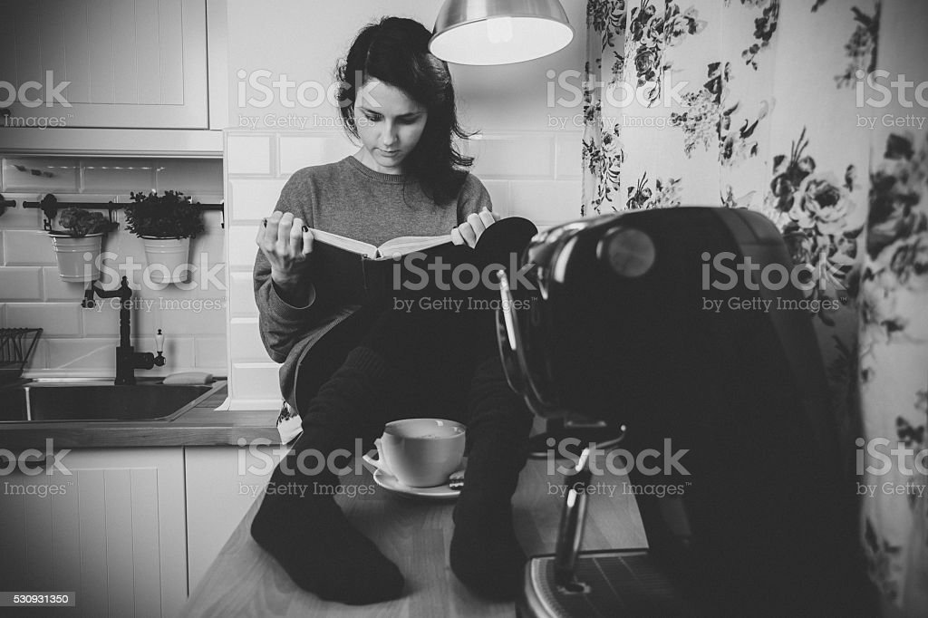 Girl in home reading a book stock photo
