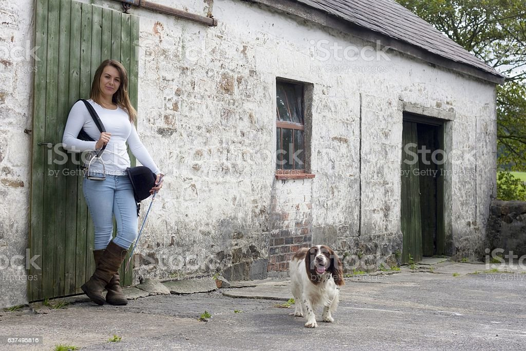 Girl in horse  riding clothes with dog stock photo
