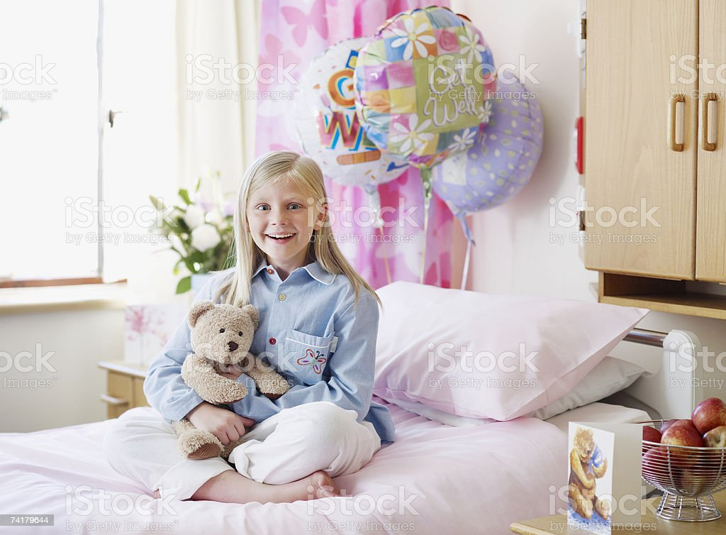 Girl in hospital with teddy bear smiling royalty-free stock photo