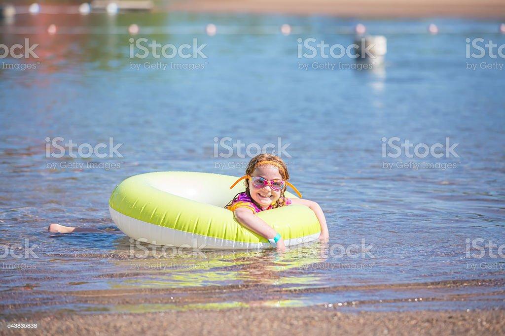 Girl In Inner Tube at Beach in Summer stock photo