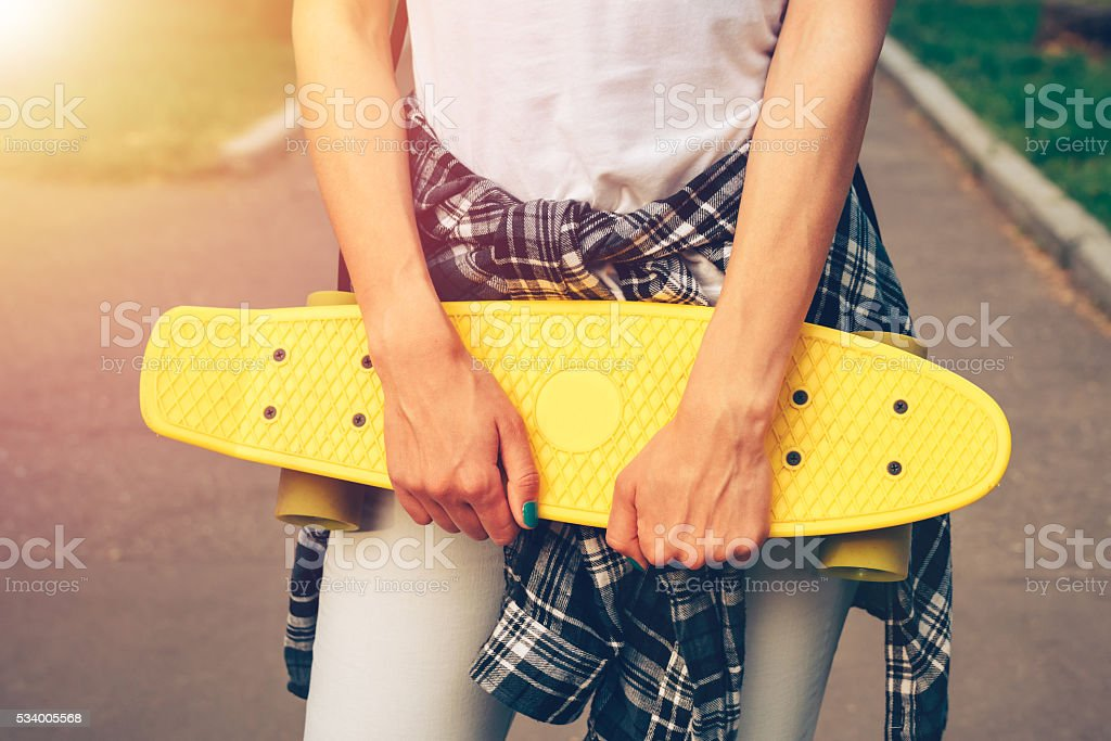 Girl in jeans and a plaid shirt holding a skateboard stock photo
