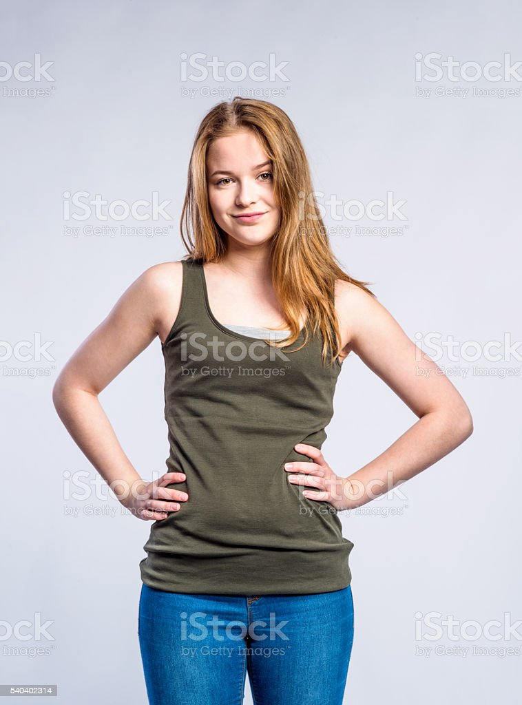 Girl in jeans and singlet, young woman, studio shot stock photo