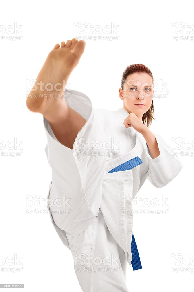 Girl in kimono demontstrating a kick stock photo