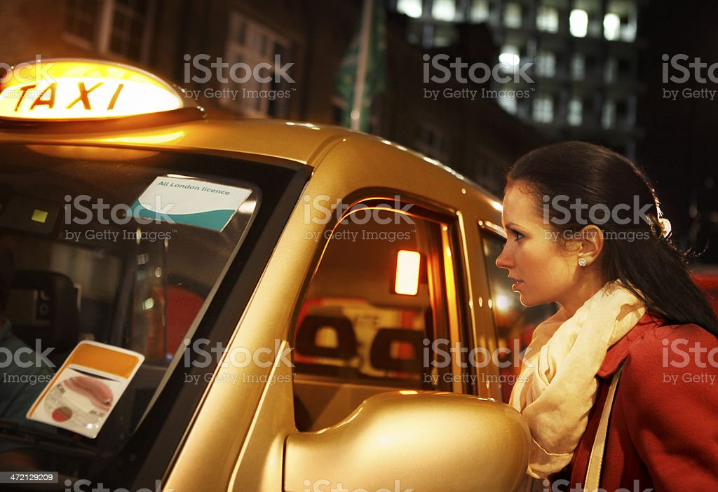 Girl in London ordering taxi by night stock photo