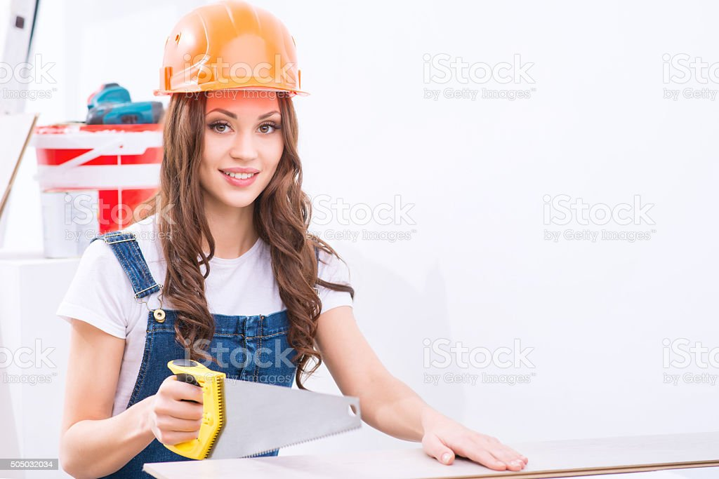 Girl in male role is busy sawing stock photo