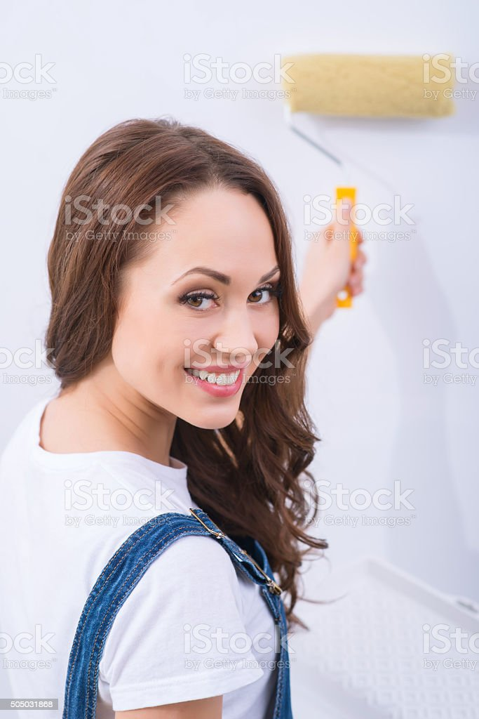 Girl in male role is painting a wall stock photo
