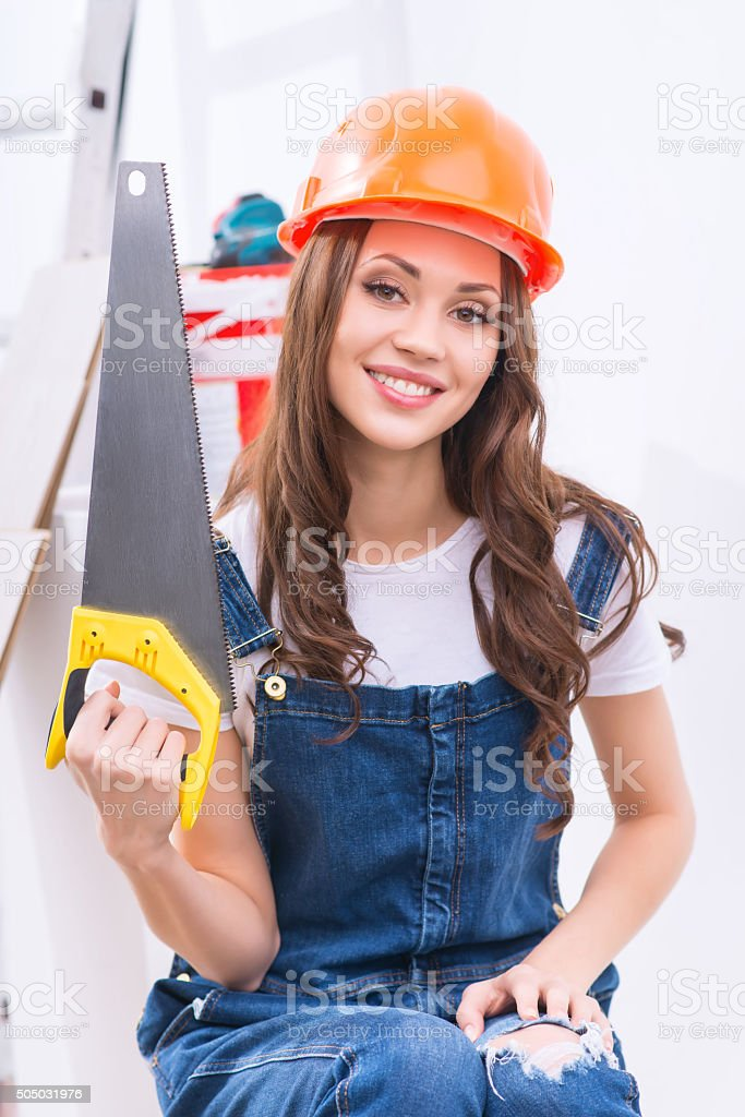 Girl in male role is upholding a saw stock photo