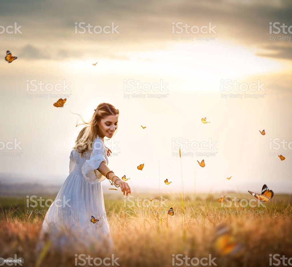 Girl in meadow with flitting butterflies stock photo