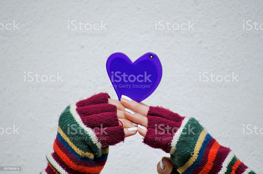 Girl in mittens holding a purple heart royalty-free stock photo