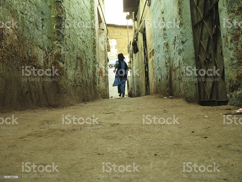 Girl in narrow alley stock photo