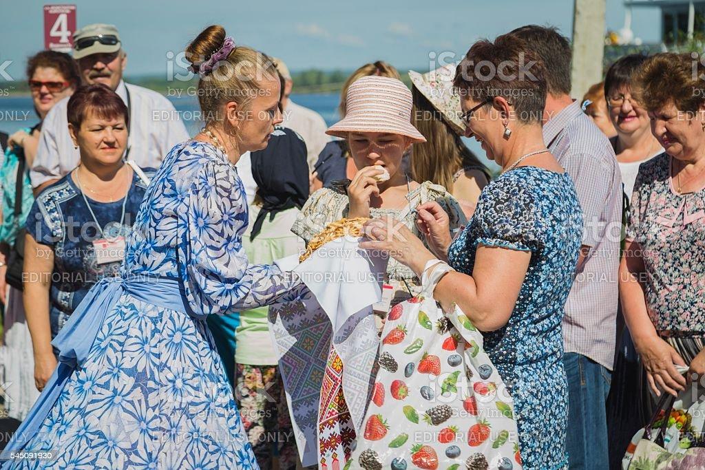 Girl in national dresses met passengers from ship stock photo