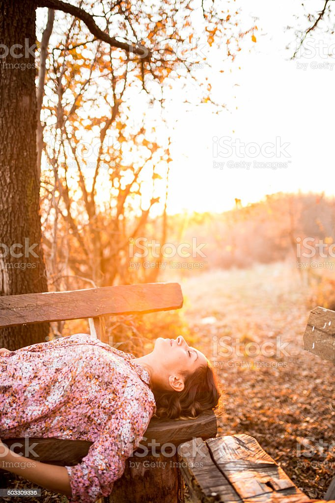 Girl in nature,lying on the bench ,eyes closed stock photo