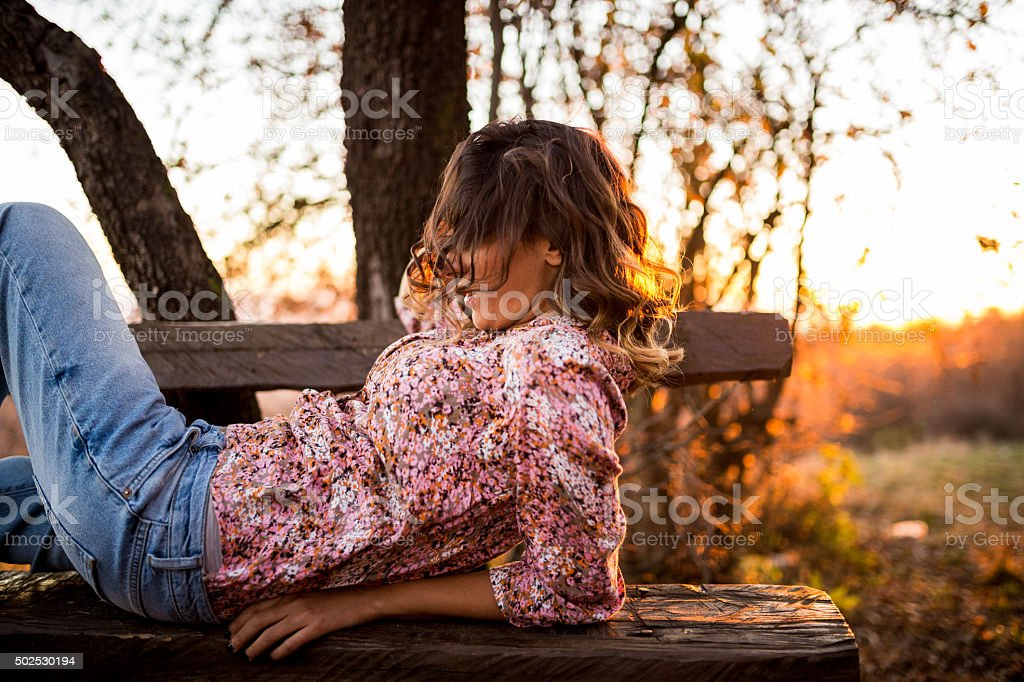 Girl in nature,lying on the bench ,fixing hair stock photo