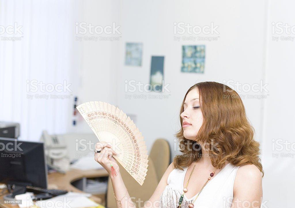 Girl in office brush away face by fan stock photo