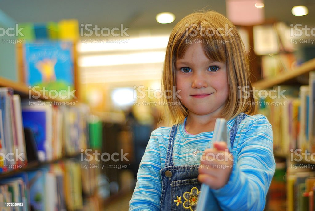 Girl in overalls showing off her book in the library stock photo