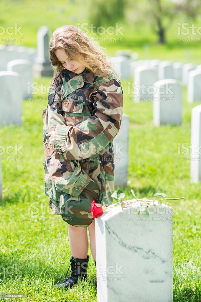 Girl in oversized army jacket at military cemetery stock photo