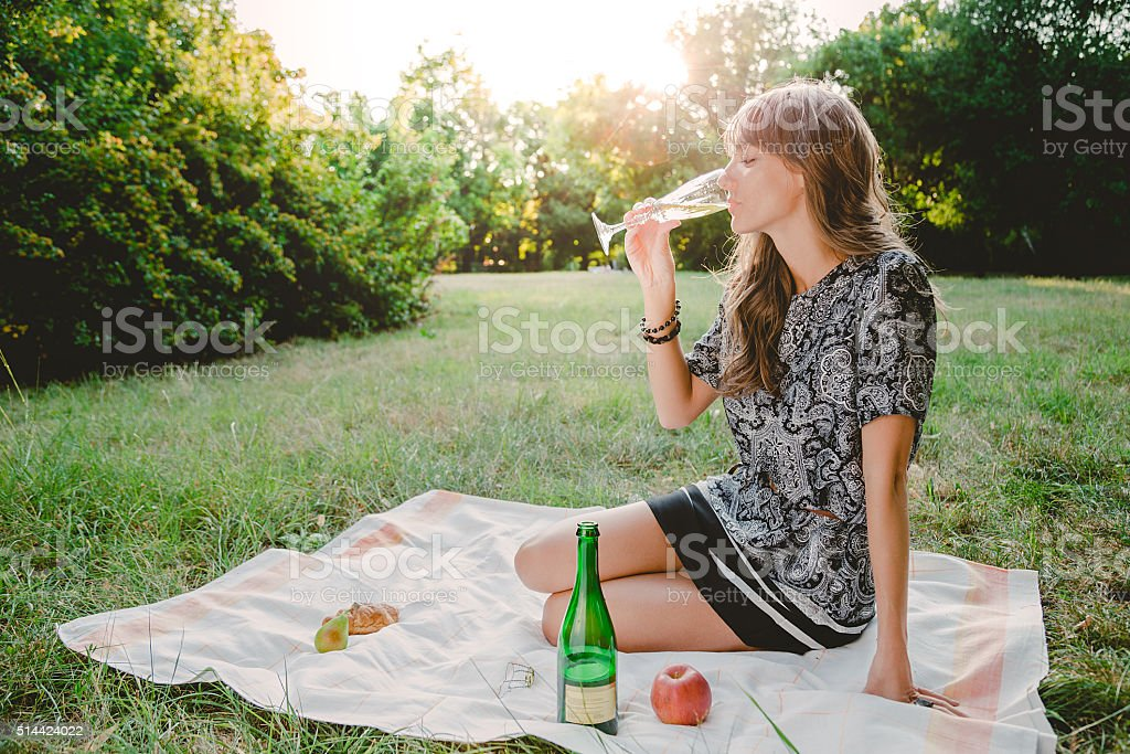 Girl in park looking at bottle of champagne stock photo