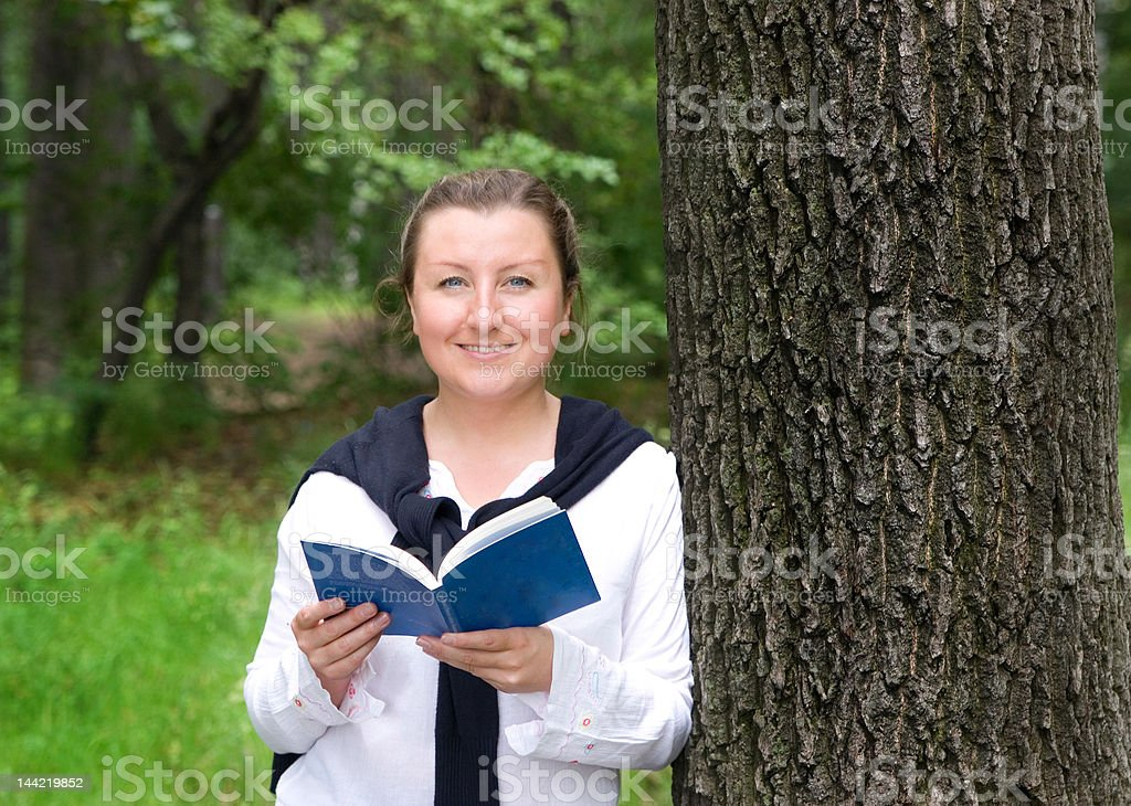 Girl in park with book royalty-free stock photo
