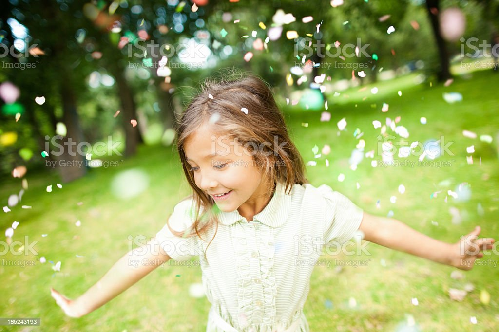 Girl In Park With Colorful Confetti Falling on Her royalty-free stock photo