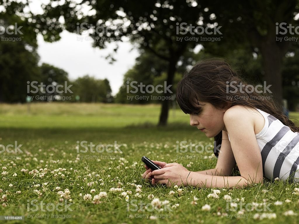 Girl in park with mobile stock photo