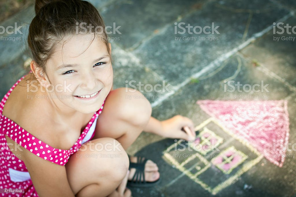 Girl in pink dress draws a house on the floor royalty-free stock photo