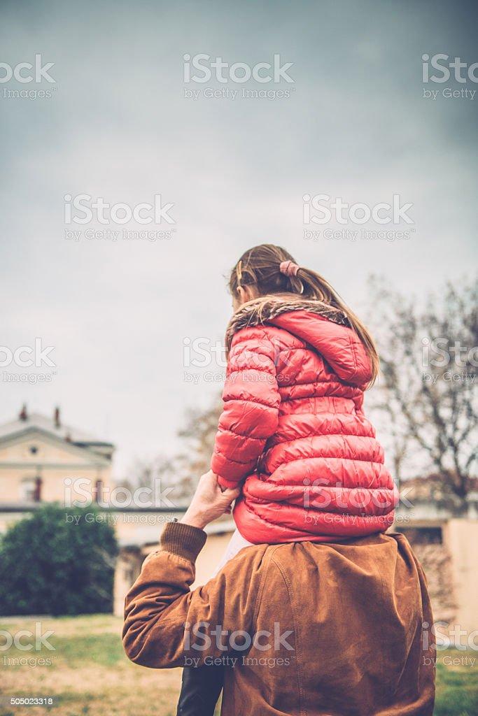 Girl in Pink Riding on Grandparent's Shoulder, Railway Station, Europe stock photo