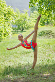 Girl in pink suit doing gymnastics in forest