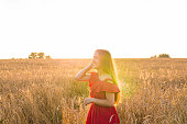 Girl in red dress on the field.