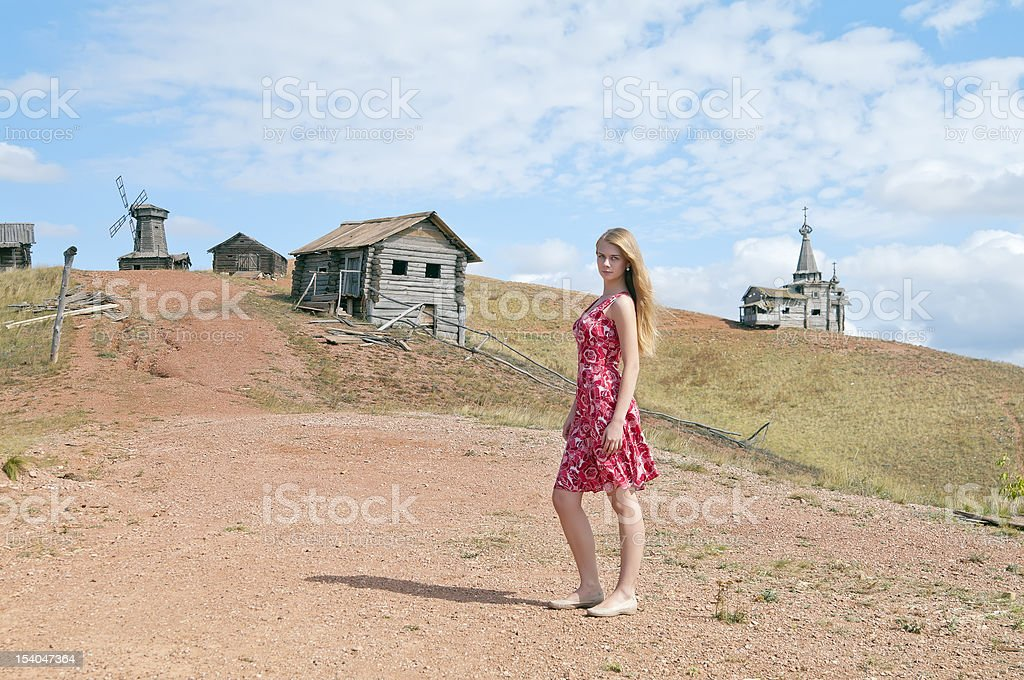 Girl in red dress on the village street stock photo