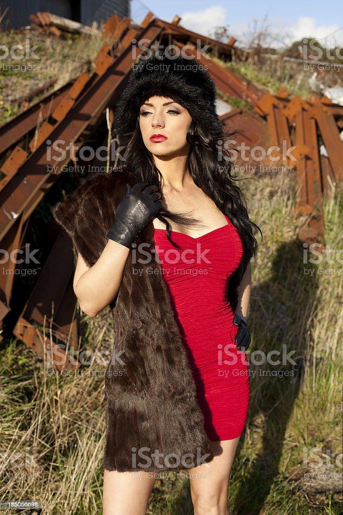 Girl in red dress wearing fur stock photo