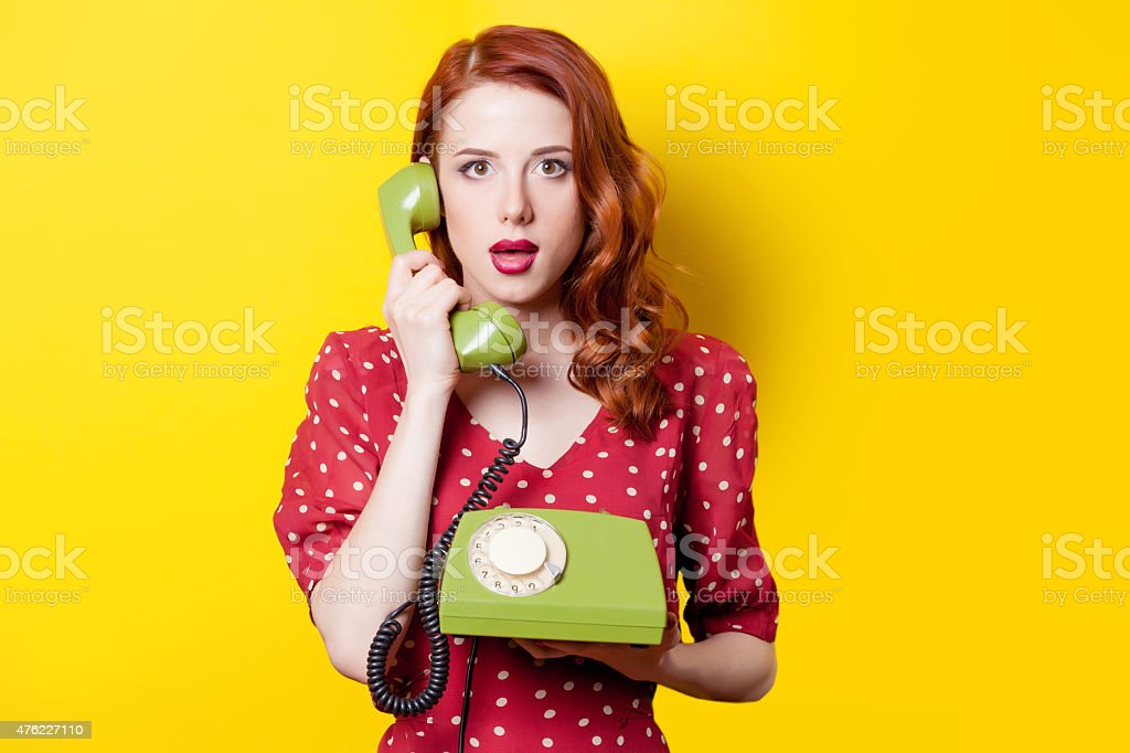 girl in red dress with green dial phone stock photo