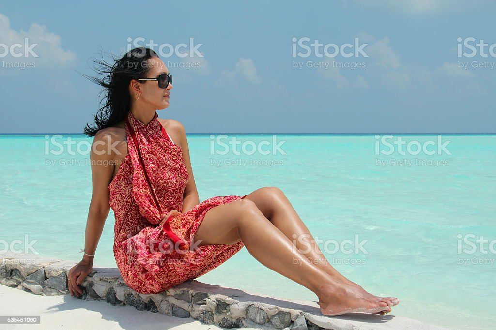 girl  in red pareo in the Maldivian beach stock photo