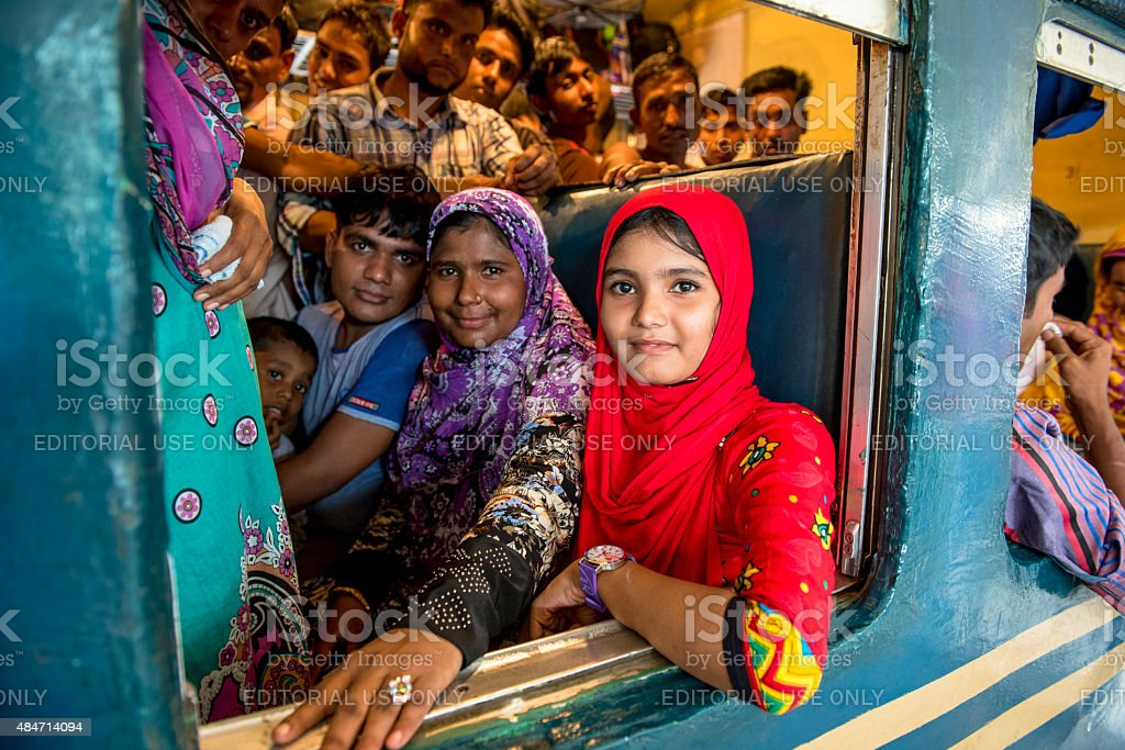 Girl in red sitting in crowded compartment, Dhaka, Bangladesh stock photo
