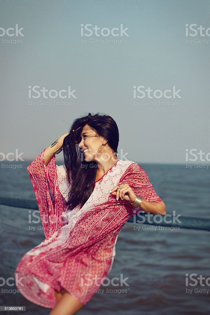 Girl in red white ornament tunic sunbathing at the seaside stock photo