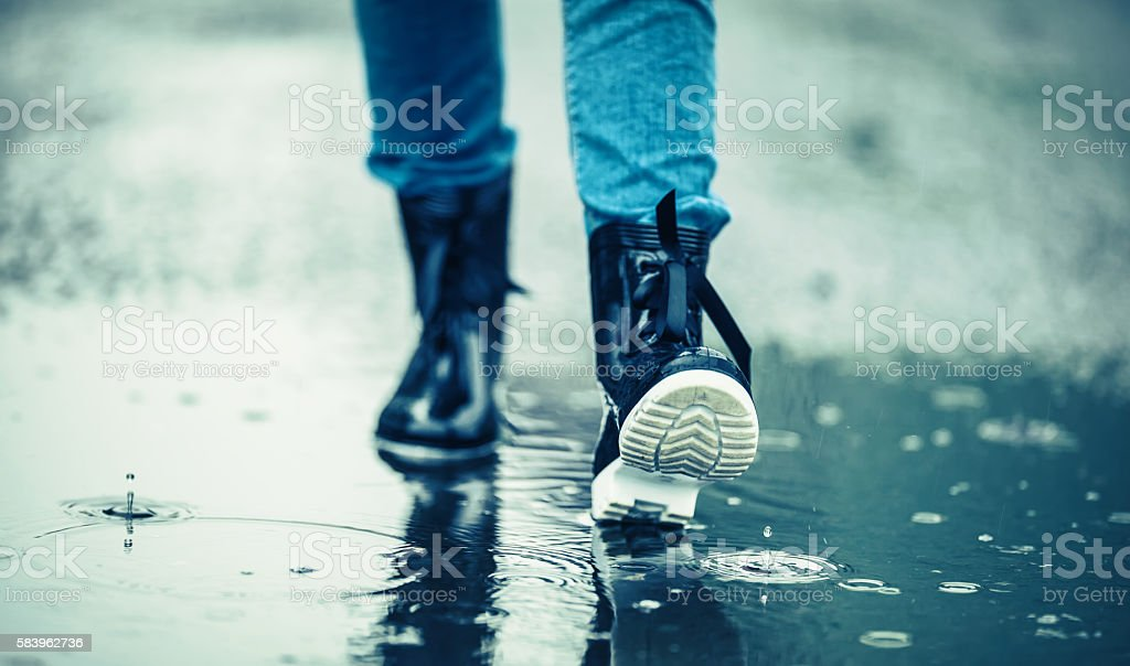 Girl in rubber boots outdoors in rainy day stock photo