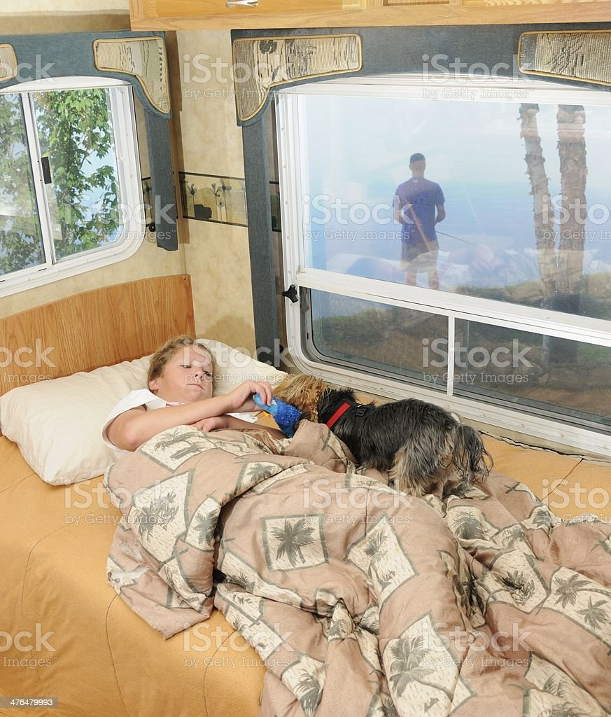Girl in RV bed playing with dog while brother fishes royalty-free stock photo